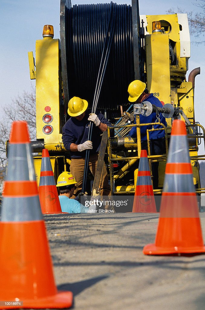 CREW LAYING ELECTRICAL CABLE : Stock Photo