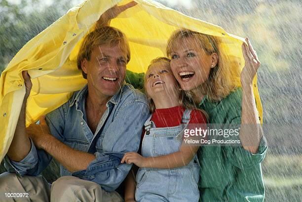 FAMILY HUDDLED UNDER JACKET IN RAIN