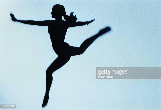 SILHOUETTE OF A FEMALE GYMNAST OR DANCER