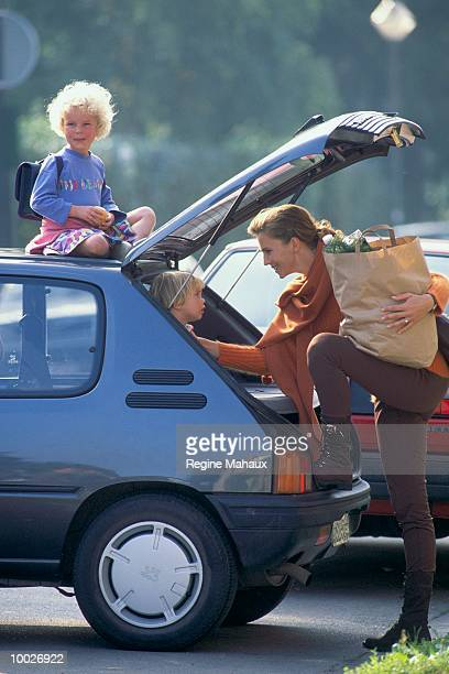 MOTHER & KIDS AT CAR AFTER SHOPPING