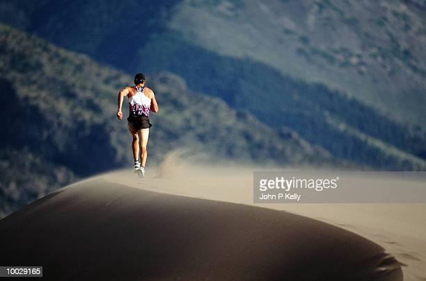 MAN RUNNING IN DUNES, GREAT SAND DUNES, COLORADO