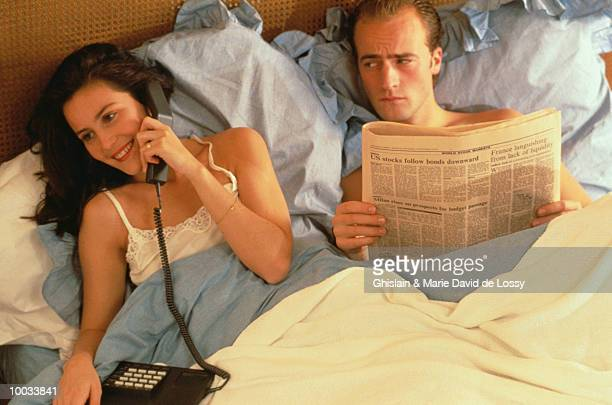 WOMAN ON PHONE & MAN READING PAPER IN BED