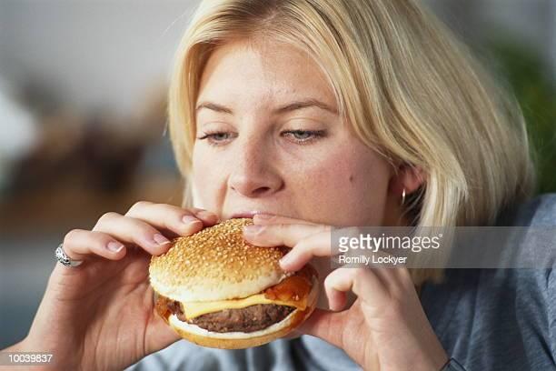 girl eating hamburger - einzelne frau über 30 stock-fotos und bilder