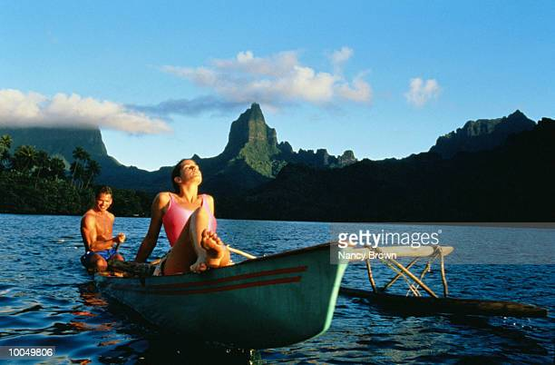 man & woman in out- rigger-moorea south pacific - femme tahitienne photos et images de collection