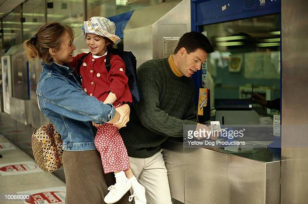 FAMILY BUYING TICKETS AT VICTORIA STATION, LONDON
