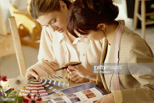 two women at home working on interior decorations - interior designer stock pictures, royalty-free photos & images