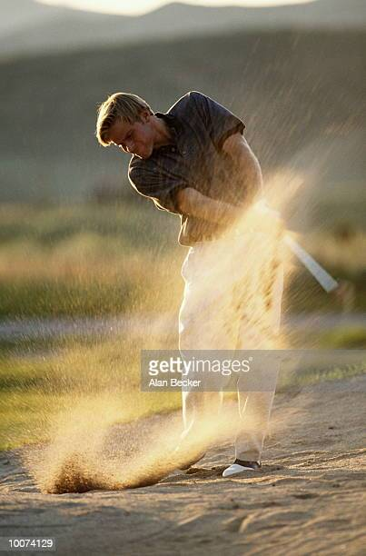 GOLF WITH YOUNG MAN IN SAND TRAP MID SWING