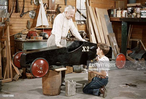 GRANDFATHER AND BOY WORK ON SOAPBOX CAR
