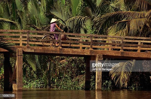 PEOPLE ON BRIDGE IN MEKONG DELTA, VIETNAM