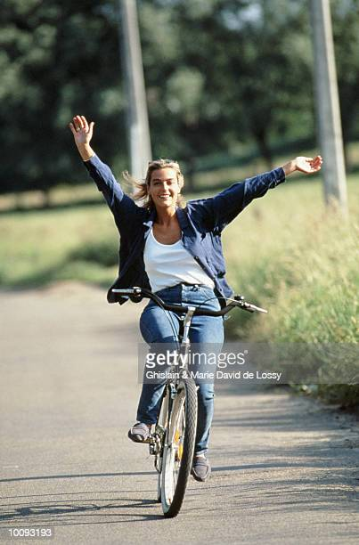 woman riding bike  with no hands - hands free cycling stock pictures, royalty-free photos & images