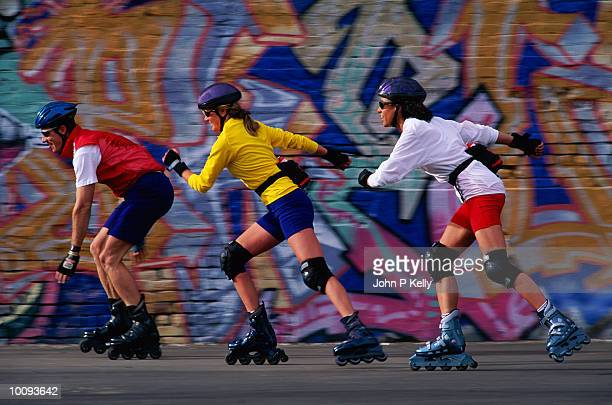 ADULTS INLINE SKATING PAST MURAL IN DENVER, COLORADO