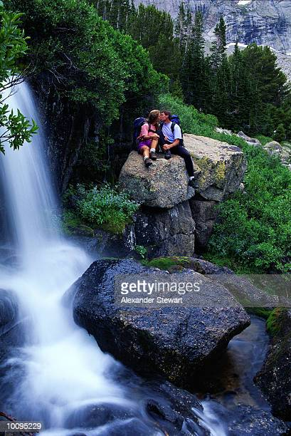 COUPLE NEAR WATERFALL AT WIND RIVER MOUNTAINS IN WYOMING