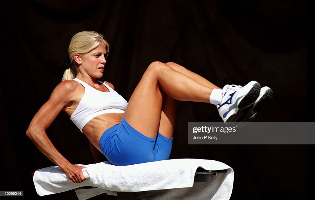 WOMAN DOING SIT-UPS IN OUTDOOR GYM : Stock Photo