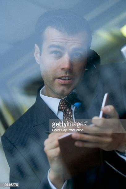 BUSINESSMAN IN PHONE BOOTH
