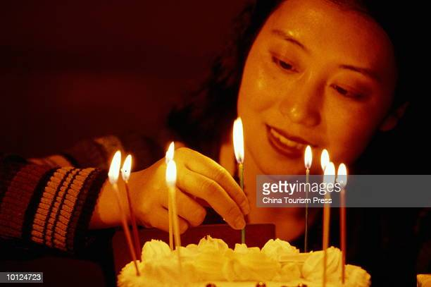 WOMAN PUTING CANDLES ON THE CAKE