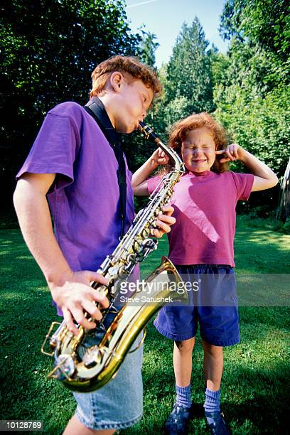 BOY AND GIRL (CAUCASION) IN OUTDOOR SETTING PLAYING SAXAPHONE
