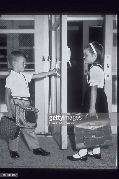 BOY HOLDS SCHOOL DOOR OPEN FOR GIRL, 1965