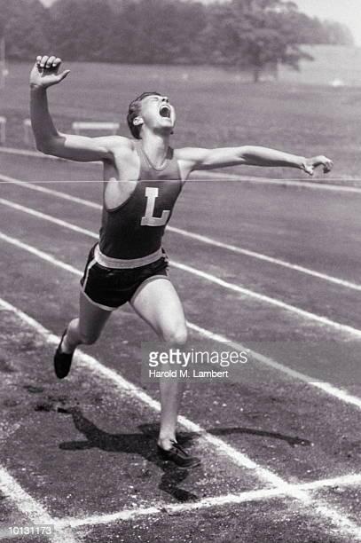 MALE RUNNER CROSSES FINISH LINE, 1958