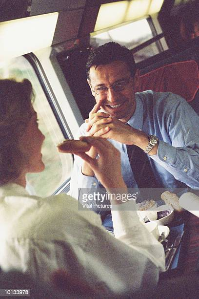 BUSINESSMAN AND WOMAN TRAIN NEWSPAPER