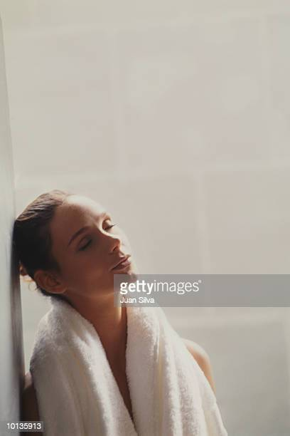 WOMAN LEANING ON WALL IN BATHROOM