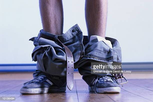 legs with pants around ankles - trousers stock pictures, royalty-free photos & images