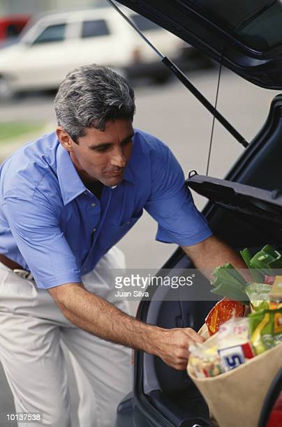 AGE 35 TO 40 COUPLE PUTTING GROCERIES IN CAR
