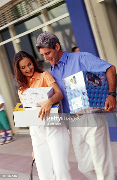 35 TO 40 COUPLE WALKING WITH BOXES AT MALL