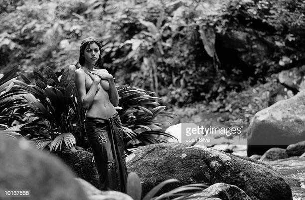 LATIN WOMAN TOPLESS WITH SARONG IN JUNGLE