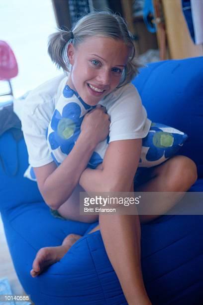 teen girl sits on sofa with flower pillow - alleen tienermeisjes stockfoto's en -beelden