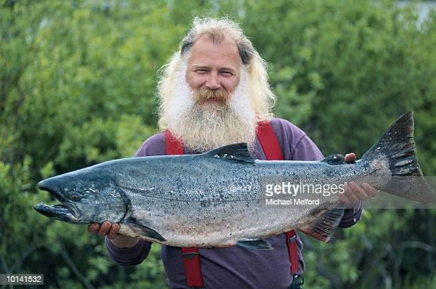 FISHERMAN WITH KING SALMON IN KENAI PENINSULA, ALASKA