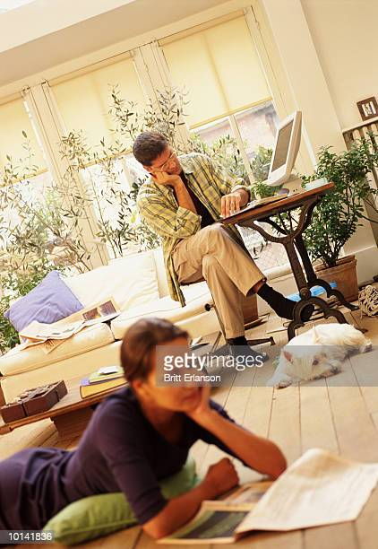 MAN O COMPUTER, DOG AND WOMAN RELAX ON FLOOR