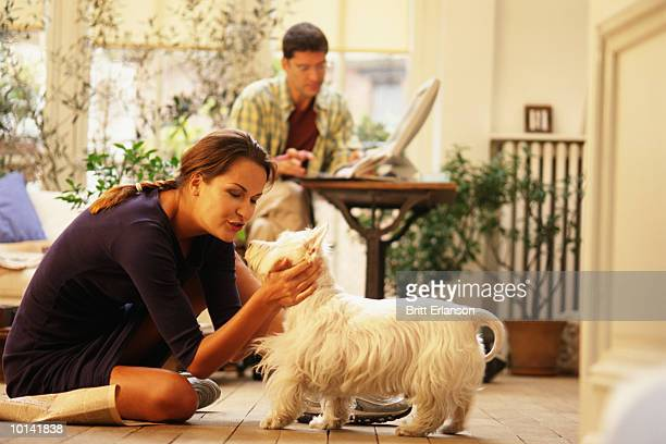 WOMAN AND DOG ON FLOOR, MAN AT COMPUTER, HOME