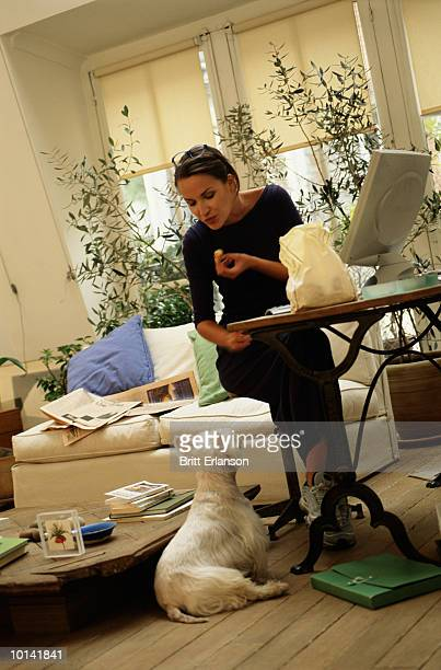 WOMAN EATS IN FRONT OF THIN COMPUTER WITH DOG