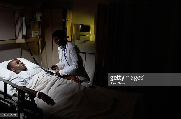 nurse taking patients blood pressure - homens de idade mediana - fotografias e filmes do acervo