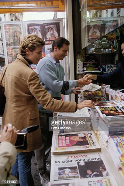 man pays for newspaper at news stand in france - news stand stock pictures, royalty-free photos & images