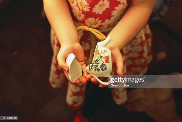 YOUNG GIRL HOLDING BROKEN TEAPOT