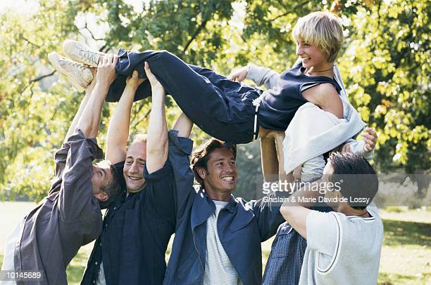 YOUNG MEN HOLDING WOMAN OVERHEAD
