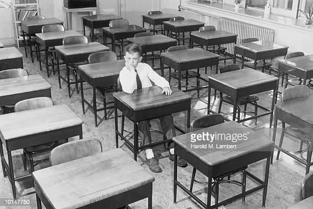 SAD BOY SITTING IN EMPTY CLASSROOM