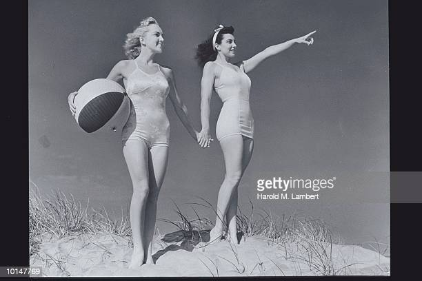 TWO WOMEN ON BEACH HOLDING HANDS, 1950