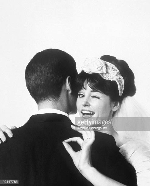 BRIDE HUGGING HUSBAND, OKAY GESTURE, 1963