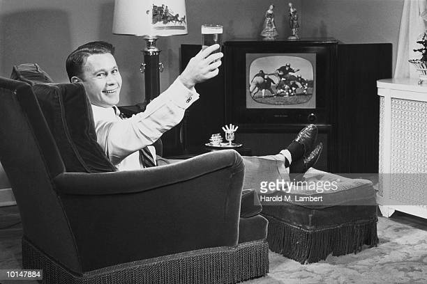 MAN WATCHING FOOTBALL GAME WITH BEER, 1959