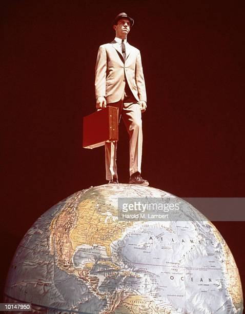 BUSINESSMAN STANDING ON TOP OF THE WORLD