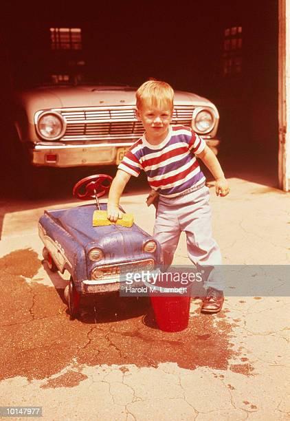 BOY WASHING HIS TOY CAR IN DRIVEWAY