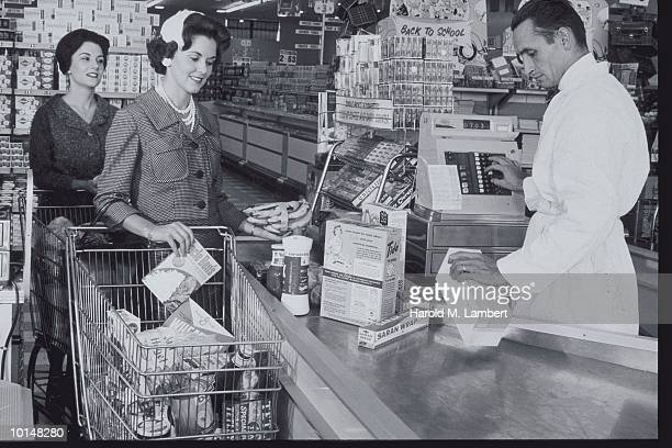 WOMAN CHECKING OUT AT GROCERY REGISTER
