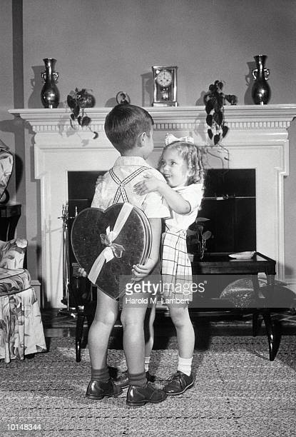 GIRL HUGS BOY WITH HEART SHAPED PRESENT, 1949