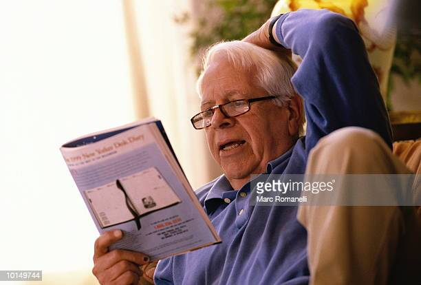 70 YEAR OLD MAN READING ON COUCH