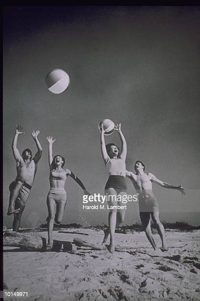 TWO YOUNG COUPLES TOSS BEACH BALLS