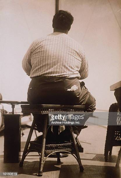 obese man sitting on wicker stool, 1930s - 人の背中 ストックフォトと画像