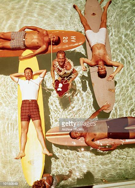 MEN ON SURFBOARDS IN POOL SIPPING DRINKS