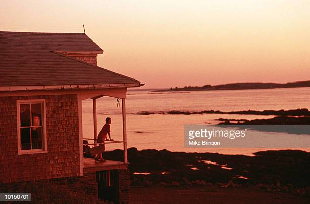 WOMAN ON PORCH OF BEACH HOUSE, MAINE
